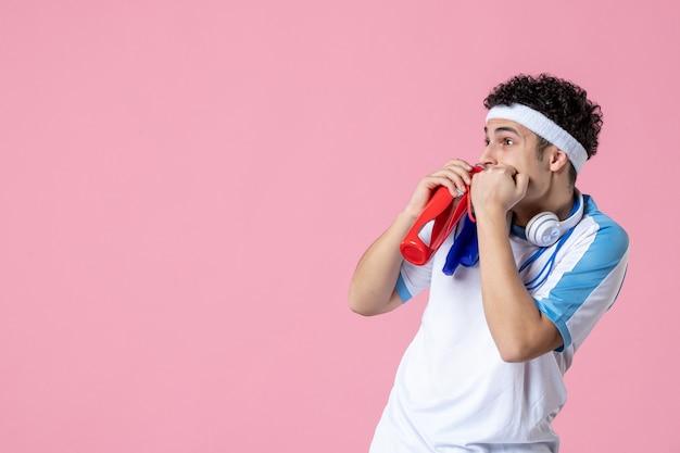 Вид спереди испуганный молодой мужчина в спортивной одежде со скакалкой и водой
