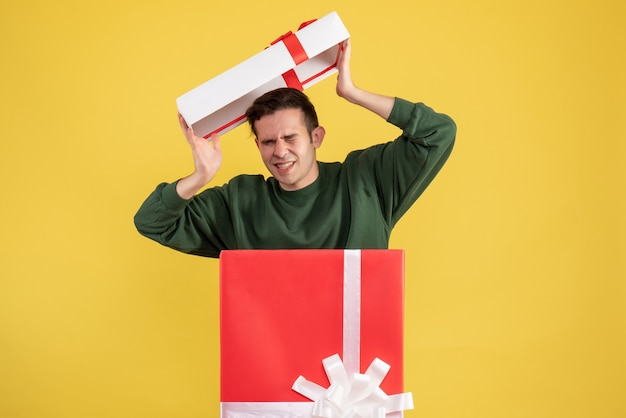 Giovane uomo spaventato di vista frontale con il coperchio della scatola che sta dietro il grande giftbox su colore giallo