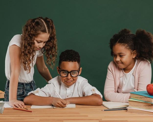 テーブルで正面図の学校の子供たち