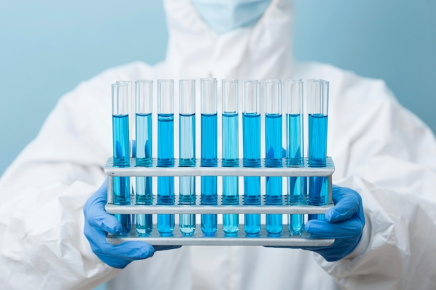 Front view scientist holding blue chemicals