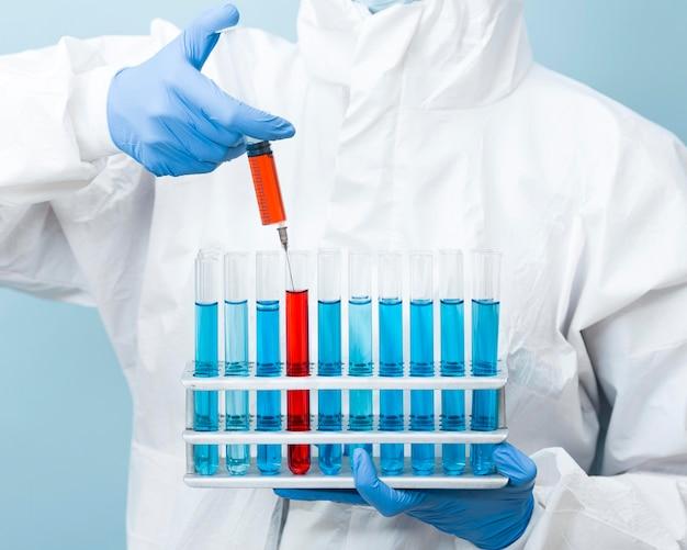 Scienziato di vista frontale che tiene i prodotti chimici nei tubi