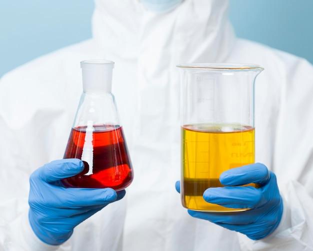 Scienziato di vista frontale che tiene diversi prodotti chimici