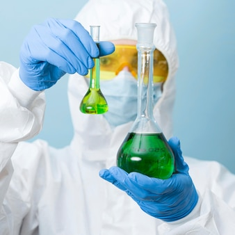 Front view scientist holding green chemicals