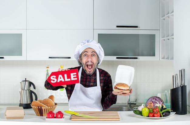 Vista frontale dello chef maschio urlante che tiene in mano il cartello di vendita e l'hamburger in cucina