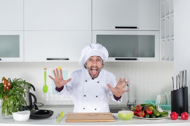 台所のテーブルの後ろに立っている制服を開いた手で男性シェフを叫んで正面図