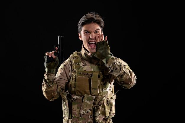Vista frontale del militare urlante in uniforme con la parete nera della pistola