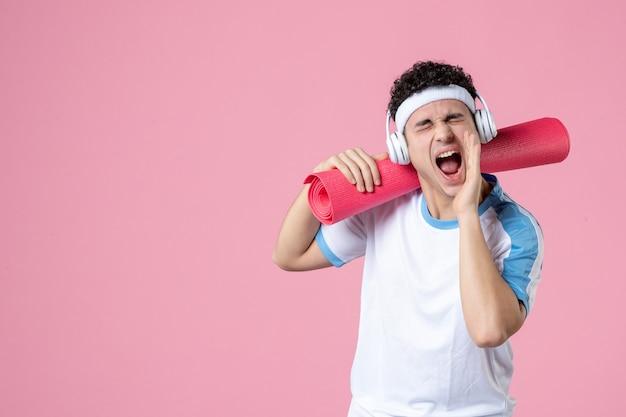 Вид спереди кричащий молодой мужчина в спортивной одежде с ковриком для йоги