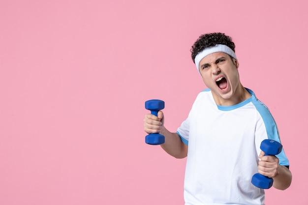 아령으로 운동하는 스포츠 옷에 젊은 남성을 비명 전면보기