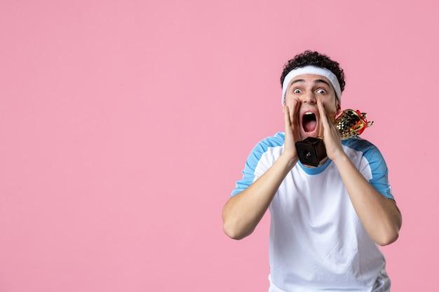 Вид спереди кричащего молодого игрока в спортивной одежде с золотой чашкой
