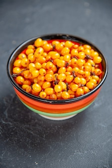 Front view sea buckthorn in bowl on dark red surface