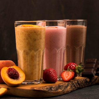 Front view of selection of milkshake glasses with fruits and chocolate