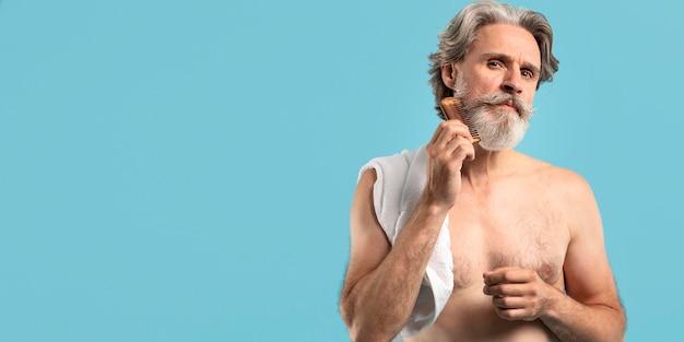 Vista frontale dell'anziano dopo la doccia che pettina la barba