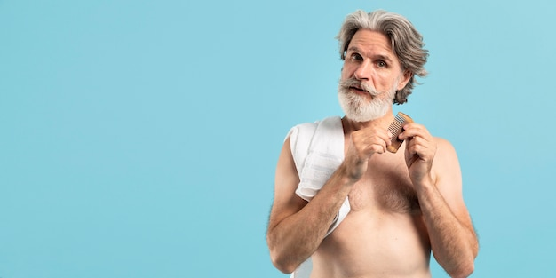 Vista frontale dell'anziano dopo il pettine della tenuta della doccia