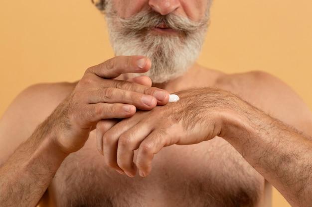 Vista frontale dell'uomo barbuto senior che applica crema