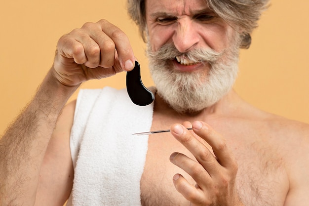 Front view of senior bearded man holding eye patches
