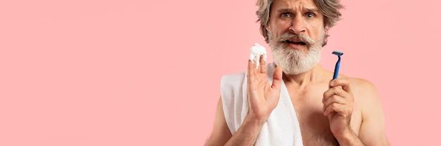 Vista frontale dell'uomo barbuto senior con la lama di rasatura