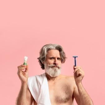 Vista frontale dell'uomo barbuto senior con schiuma da barba e lama