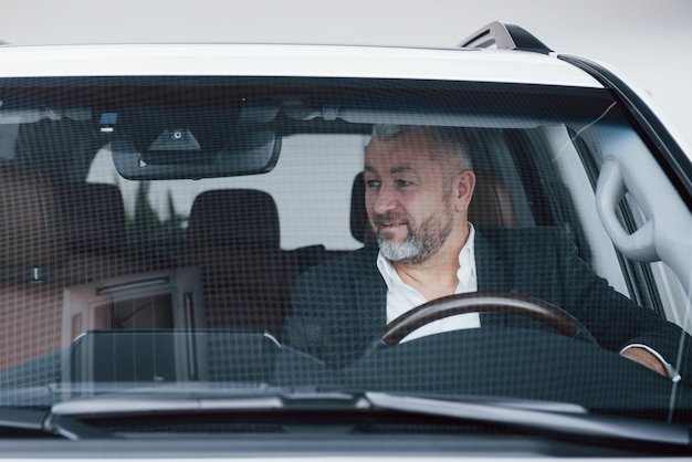 Front view of senior businessman in his new modern car testing new functions