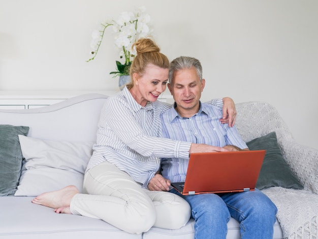 Front view senior couple on a couch with notebook