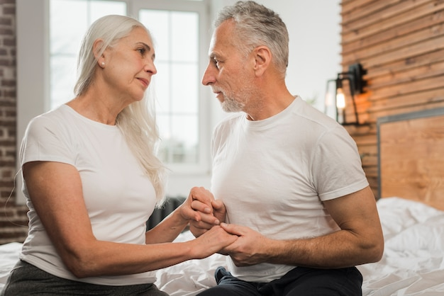 Front view senior couple holding hands
