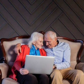 Front view senior couple holding a laptop