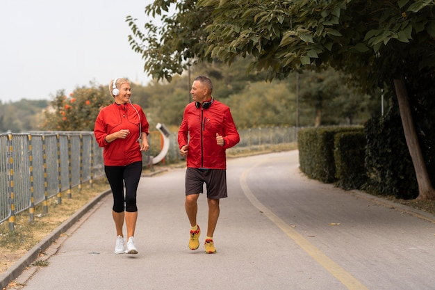 Front view of senior couple jogging together outside in the park
