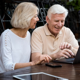 Front view of senior couple out in the city with laptop and tablet