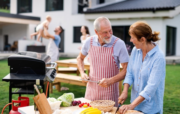 Front view of senior couple with family outdoors on garden barbecue, grilling.