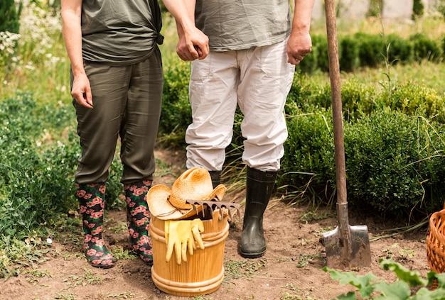Вид спереди старшая пара с садовыми принадлежностями