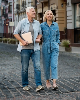 Front view of senior couple with tablet taking a walk in the city