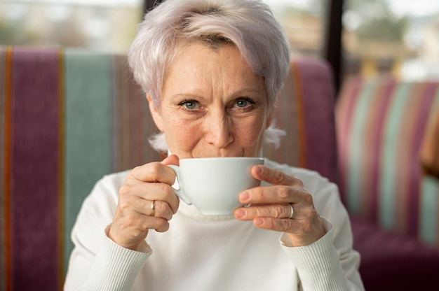 Front view senior female drinking coffee