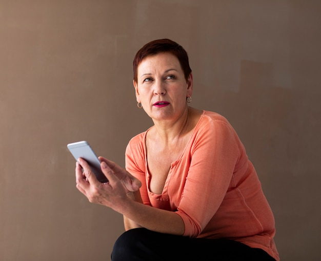 Front view senior lady holding smartphone