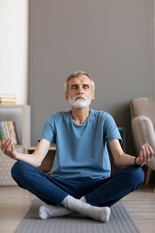 Front view senior male meditating