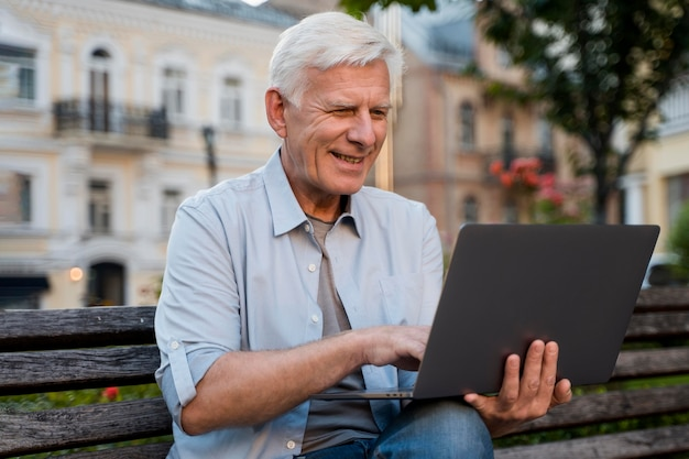 Front view of senior man outdoors on bench with laptop