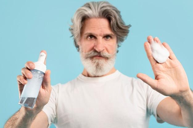 Vista frontale dell'uomo maggiore che mostra detergente