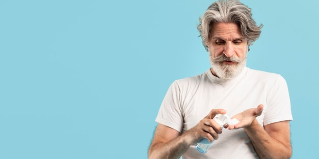 Vista frontale dell'uomo senior che usando pulitrice