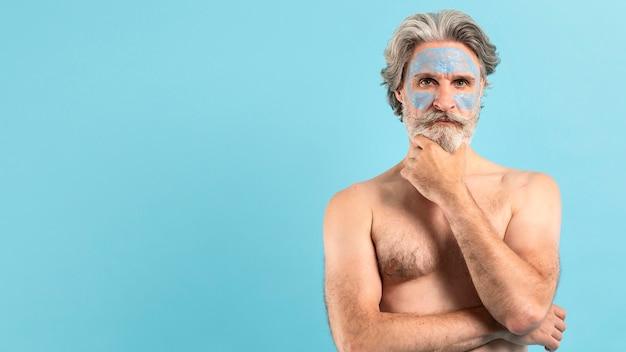 Vista frontale dell'uomo senior che usando la maschera di protezione