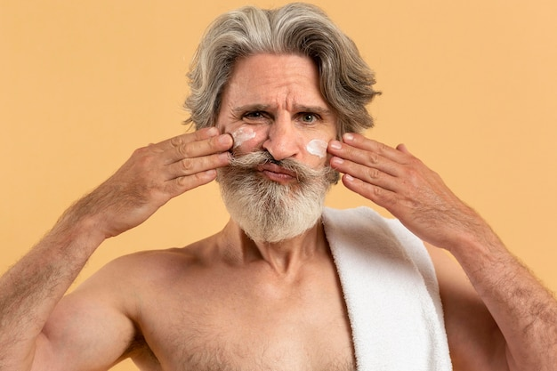 Front view of senior man with beard applying cream on face