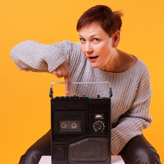 Front view senior woman holding vintage cassette player
