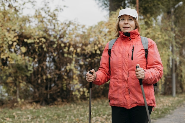 Front view of senior woman trekking outdoors with copy space