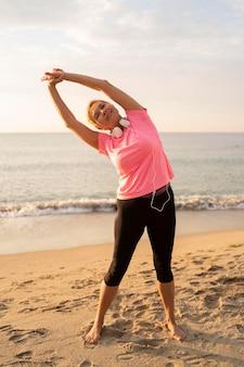Vista frontale della donna senior con le cuffie che si estende sulla spiaggia