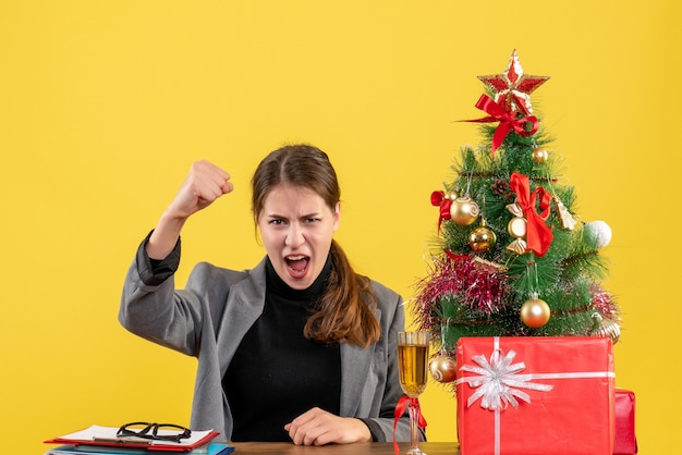 Вид спереди серьезная девушка, сидящая за столом с жестом `` давай, сражайся со мной '' возле рождественской елки и подарочного коктейля
