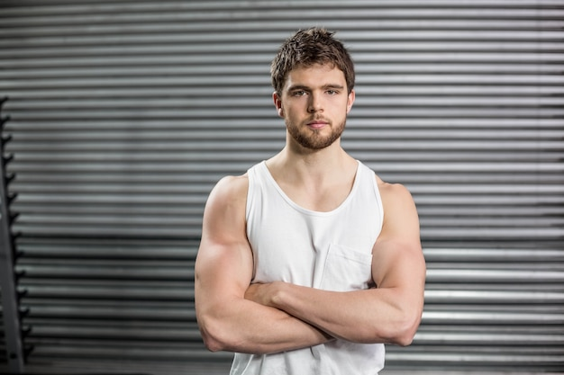 Front view of serious man crossing arms at gym