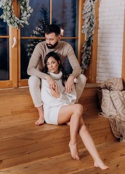La vista frontale di un uomo serio abbraccia la sua affascinante ragazza seduta sulle scale di legno