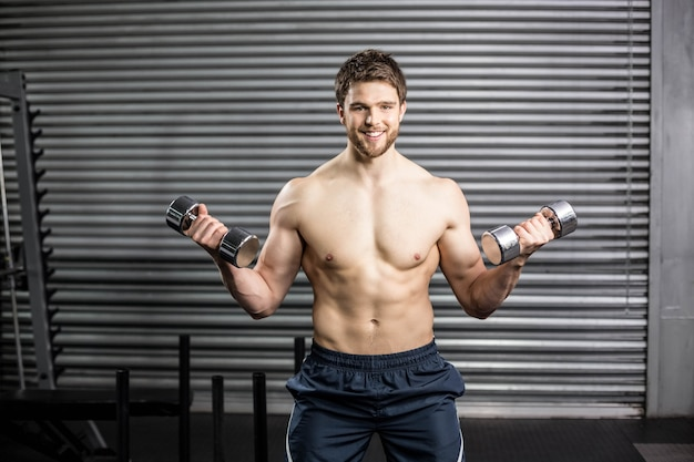 Front view of serious man lifting weight at gym