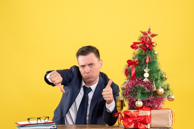 Front view of serious man making thumb up and down sign sitting at the table near xmas tree and gifts on yellow