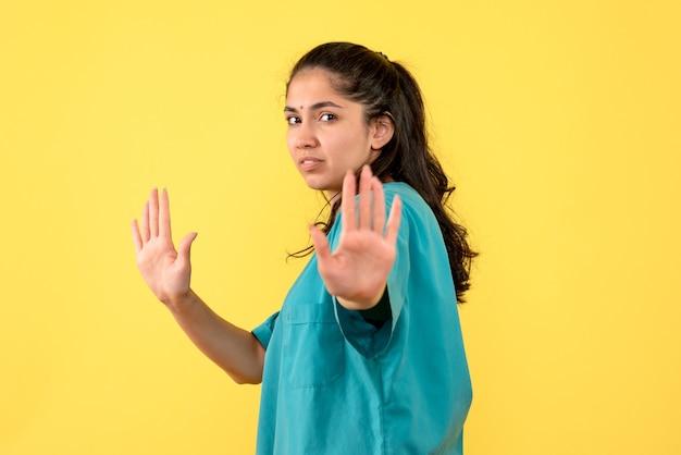 Medico femminile abbastanza serio di vista frontale che prova a fermare qualcosa su priorità bassa gialla