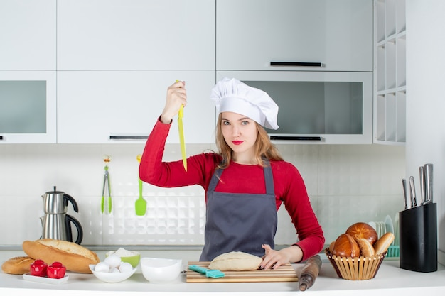Front view serious woman in cook hat holding up knife in the kitchen