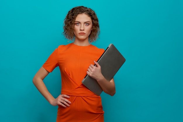 Front view of serious woman keeping computer in hands