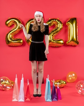 Vista frontale seria giovane donna in abito nero che punta alle borse a sinistra sui palloncini del pavimento su rosso